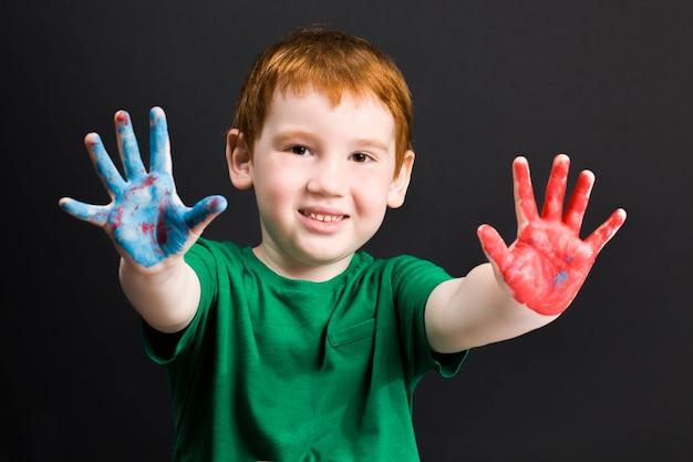 Портрет маленького рыжеволосого мальчика рисует на бумаге красками разных цветов, которые мальчик рисует руками