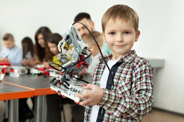 コンピューターでプログラムされたプラスチック部品から組み立てたロボットを持った、学校のロボット工学のクラスの賢い少年の肖像画。