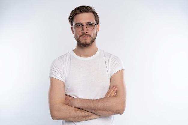 白い背景に立っている眼鏡のスマートな若い男の肖像画。