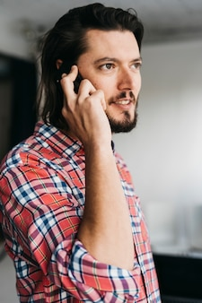 Portrait of a smart young man in plaid shirt talking on cell phone