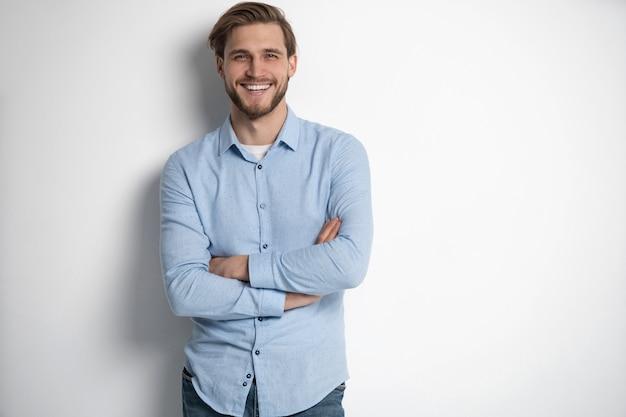 白い背景に立っているスマートな若い男の肖像画。