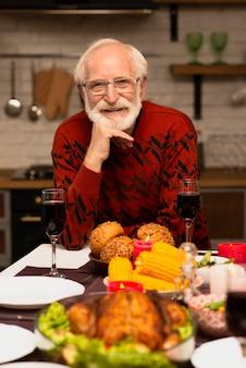 Портрет улыбающегося пожилого мужчины за столом