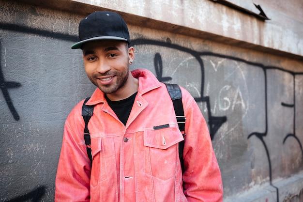 Портрет улыбающегося африканского парня в кепке с рюкзаком