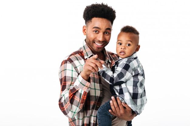 彼の幼い息子を保持している笑顔のアフリカ人の肖像画