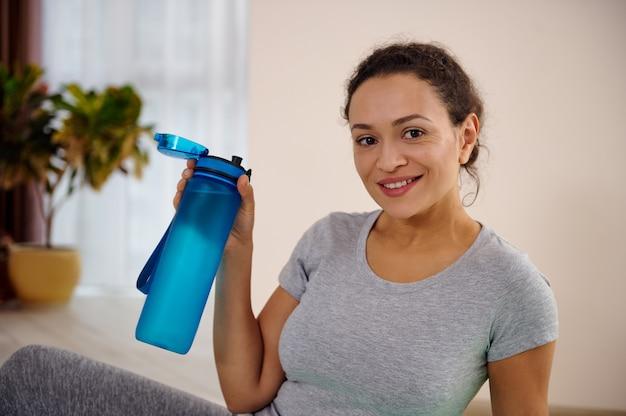 집에서 운동 후 물 한 병을 들고 웃는 아프리카 여자의 초상화