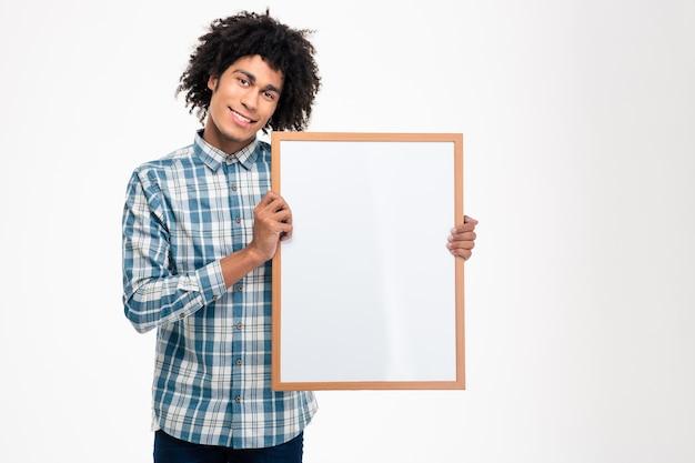 Портрет улыбающегося афроамериканца, держащего пустую доску, изолированную на белой стене