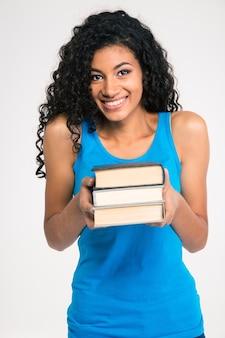 흰 벽에 고립 된 책을 들고 웃는 아프리카 미국 여자의 초상화