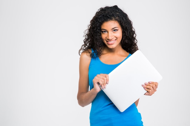 白い壁に隔離されたラップトップコンピューターを保持している笑顔のアフリカ系アメリカ人女性の肖像画