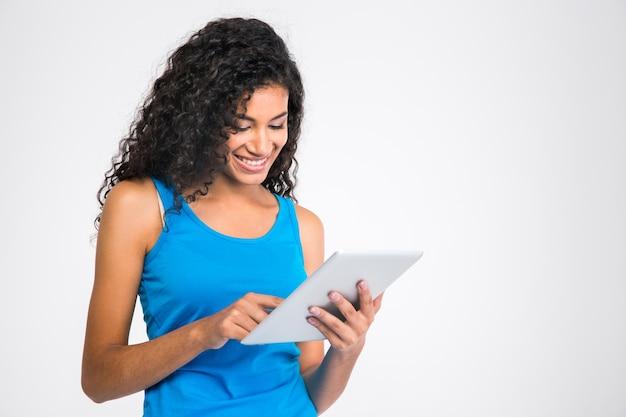 白い壁に分離されたタブレットコンピューターを使用して笑顔のアフリカ系アメリカ人女性の肖像画