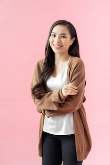Портрет улыбающейся азиатской бизнес-леди, стоящей со сложенными руками и смотрящей в камеру, изолированную на розовом фоне