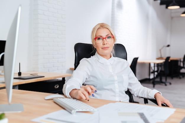 オフィスでラップトップを使用して笑顔の魅力的な成熟した実業家の肖像画