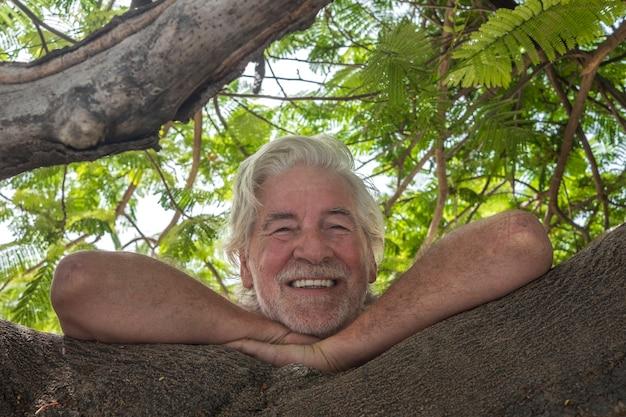 나무 가지에 기대어 자연과 식물을 즐기는 수염을 기른 매력적인 은퇴한 남자의 초상화 - 은퇴자를 위한 활동적인 생활 방식