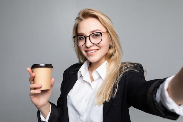 分離されたテイクアウトのコーヒーカップを押しながらselfieを取るスーツで笑顔の魅力的な女性の肖像画