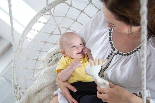 Портрет улыбающегося ребенка в желтой футболке с мамой на руках в кресле-гамаке.