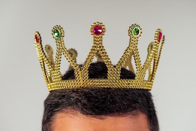 Портрет улыбающегося бородатого делового человека с золотой короной на голове на белом фоне студийный снимок