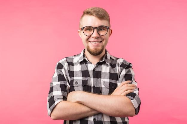 Портрет улыбающегося бородатого мужчины в очках, смотрящего в камеру на розовом фоне