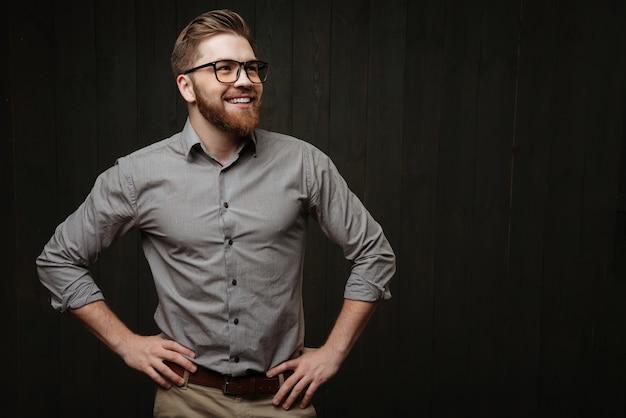 Портрет улыбающегося бородатого мужчины в очках, стоящего с руками на бедрах и смотрящего в сторону, изолированного на черной деревянной поверхности