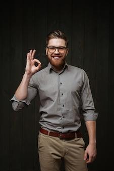 Портрет улыбающегося бородатого мужчины в очках и рубашке, демонстрирующего нормальный жест, изолированный на черной деревянной поверхности