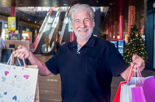 家族や友人への贈り物と一緒にたくさんのバッグを持ってカメラを喜んで見ながら、モールでクリスマスの買い物をしている笑顔のひげを生やした年配の男性の肖像画