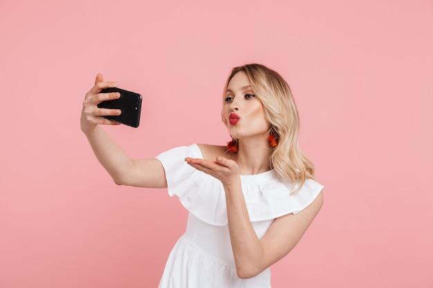 ピンクの上に孤立して立って、selfieを取り、キスを送信する夏のドレスを着て笑顔の美しいブロンドの女性の肖像画