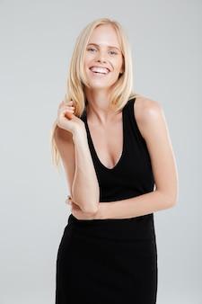 Портрет улыбающейся красивой счастливой женщины, стоящей на белом фоне и смотрящей в камеру