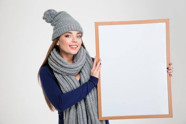 흰색 배경에 고립 된 빈 보드를 보여주는 웃는 아름 다운 여자의 초상화
