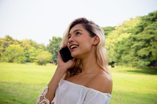 Портрет улыбающейся красивой женщины текстовых сообщений и разговора по телефону