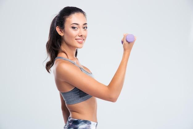 Портрет улыбающейся красивой женщины, тренирующейся с гантелями, изолированной на белой стене