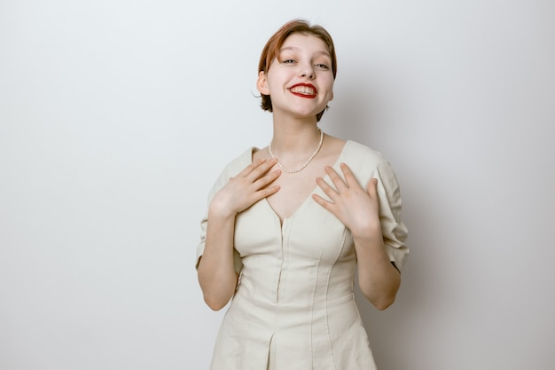 Портрет улыбающейся красивой молодой девушки с красными губами и большими глазами. светлый фон.