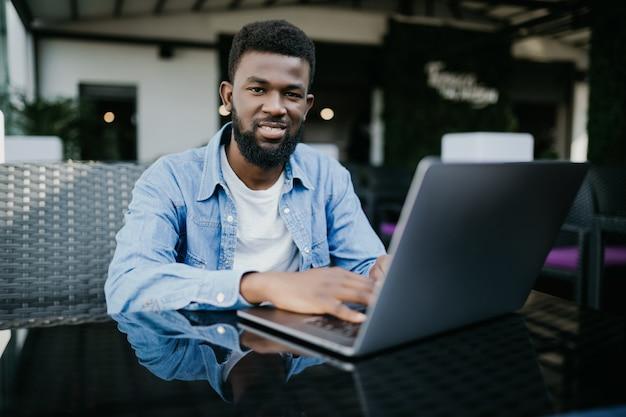Портрет улыбающегося черного бизнесмена с ноутбуком в кафе