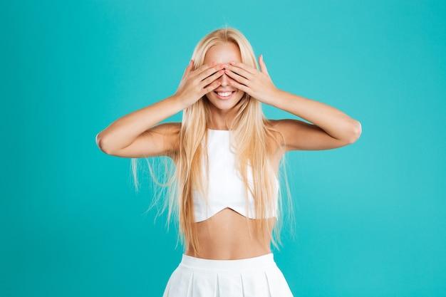 笑顔のブロンドの女の子の肖像画は、青い背景で隔離の手のひらで彼女の目を覆います
