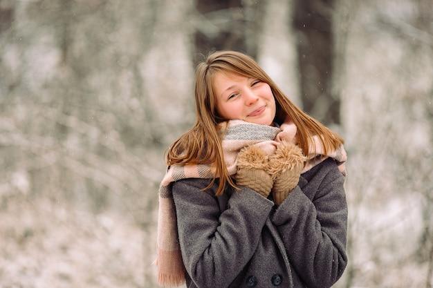 따뜻한 스카프와 겨울 숲에서 장갑에 웃는 금발 소녀의 초상화.