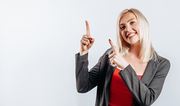 白の上に指を指している笑顔の金髪の女性の肖像画