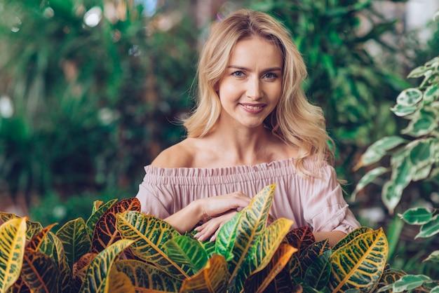 庭のクロトンの葉の後ろに立っている笑顔金髪の若い女性の肖像画