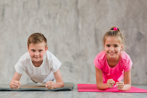 Портрет улыбающегося мальчика и девочки делают упражнения перед бетонной стеной