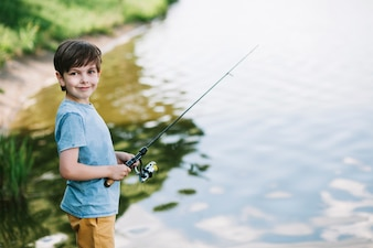 Portrait of a smiling boy fishing on lake