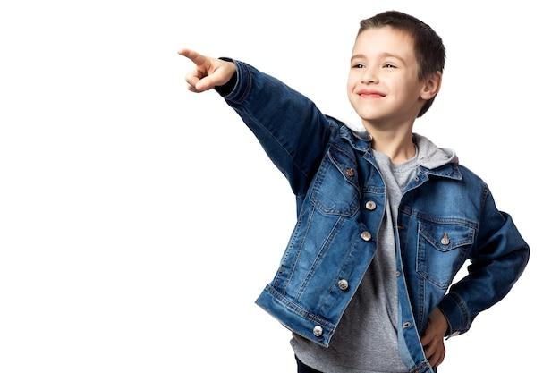 데님 재킷에 웃는 소년의 초상화는 방향을 가리키고 그의 업적에 기뻐하며 흰색 격리 된 배경에 재미를 가지고 있습니다.