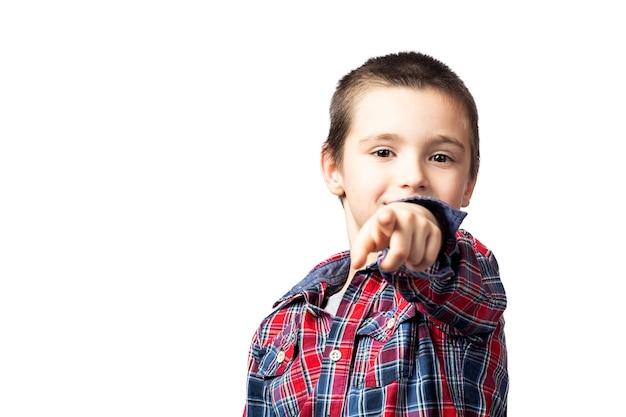 격자 무늬 셔츠에 웃는 소년의 초상화는 카메라를 가리키고, 흰색 격리 된 배경에 재미가