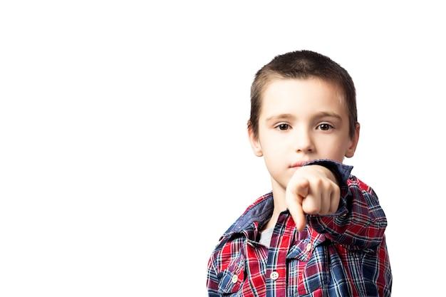 격자 무늬 셔츠에 웃는 소년의 초상화는 격리 된 흰색 배경에 카메라를 가리 킵니다