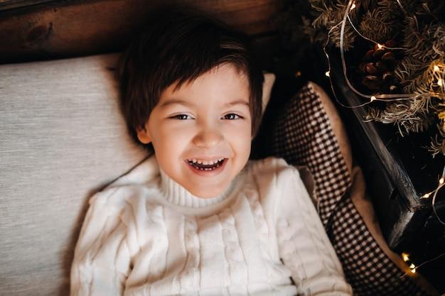 自宅のクリスマスツリーに横たわっている笑顔の少年の肖像画。