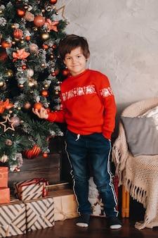 自宅のクリスマスツリーに立っている笑顔の少年の肖像画。