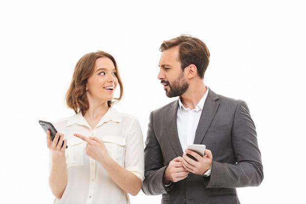 Портрет улыбающейся деловой пары, держащей мобильные телефоны