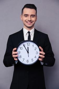 Портрет улыбающегося бизнесмена, держащего настенные часы над серой стеной