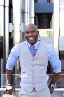 オフィスビルの隣にスーツを着て笑顔のビジネスマンの肖像画。