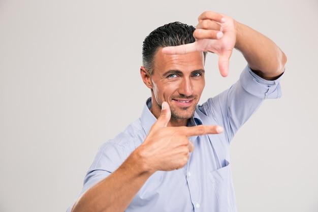 Портрет улыбающегося бизнесмена, делающего рамку пальцами над серым пространством