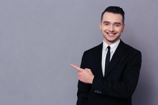 Портрет улыбающегося бизнесмена, показывающего пальцем над серой стеной