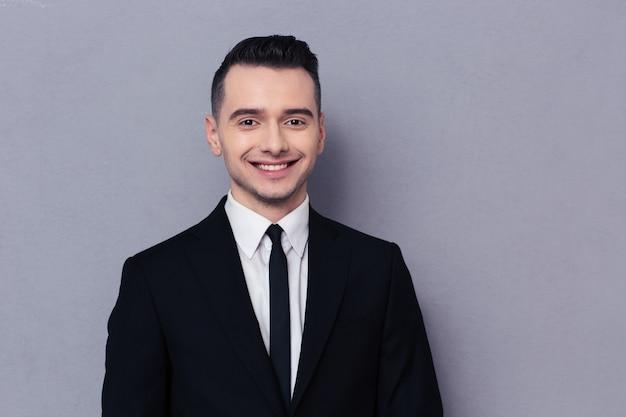 Портрет улыбающегося бизнесмена, стоящего над серой стеной и