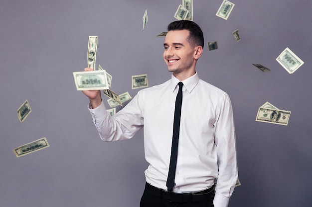 Портрет улыбающегося бизнесмена, стоящего под дождем с деньгами над серой стеной