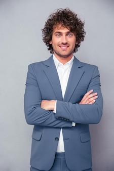 Портрет улыбающегося бизнесмена, стоящего со скрещенными руками над серой стеной