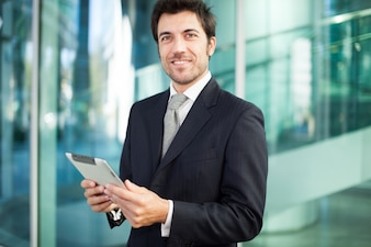 彼のタブレットコンピュータを使って笑っている実業家の肖像